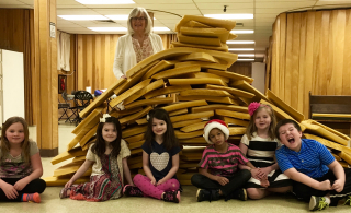 Karen and children build a tower of Babel.